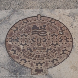 View NE from NA-6062 (El Camino - at intersection with C/ Jardín) down to ornate manhole cover - Muruzábal - Day 4